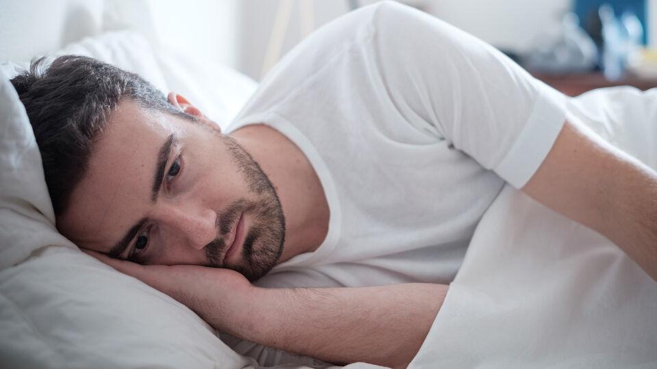 Mann Bett Schlaflos - Wer Probleme mit dem Einschlafen hat, sollte seine Schlafhygiene unter die Lupe nehmen. Entfernen Sie alle Störfaktoren. Ideal ist ein ruhiges, kühles und abgedunkeltes Schlafzimmer. Führen Sie feste Schlafrituale ein und verbannen Sie Handy, Tablet & Co. aus dem Bett. - © Shutterstock